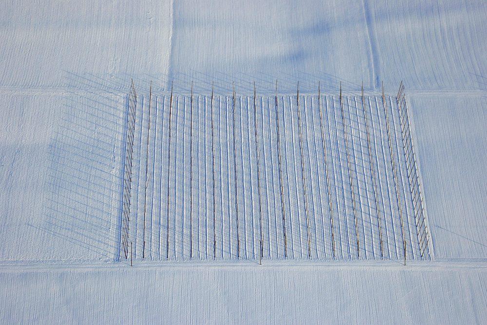 Luftaufnahme von den Stangen eines Hopfenfeldes auf einem verschneiten Feld.